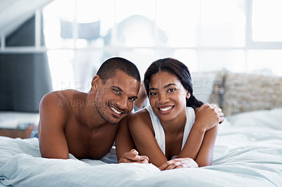 Buy stock photo Portrait of a smiling young couple lying on their bed at home
