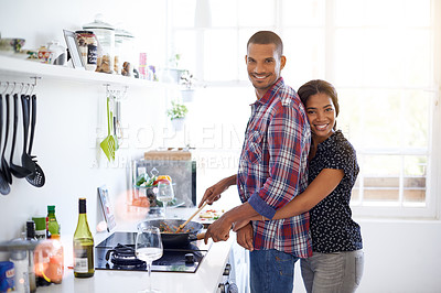 Buy stock photo Portrait of a young couple cooking a meal together in their kitchen