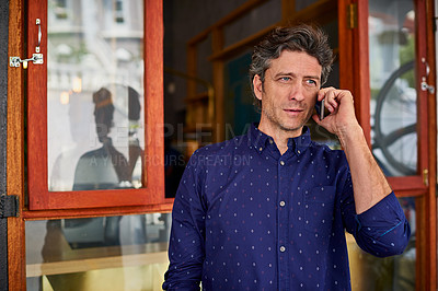 Buy stock photo Shot of a man talking on his cellphone wile standing in front of a cafe