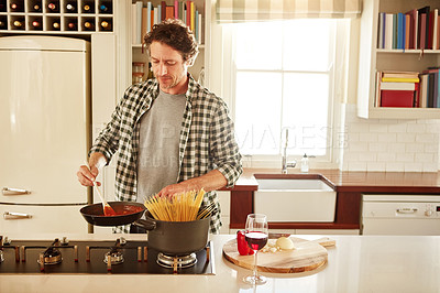 Buy stock photo Shot of a man cooking in his kitchen