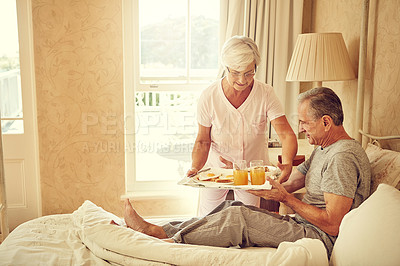 Buy stock photo Shot of a senior woman bringing breakfast in bed to her husband