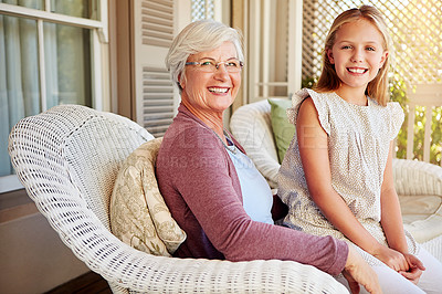 Buy stock photo Cropped portrait of a young girl sitting outside with her grandmother