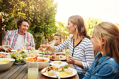 Buy stock photo Shot of a family eating lunch together outdoors