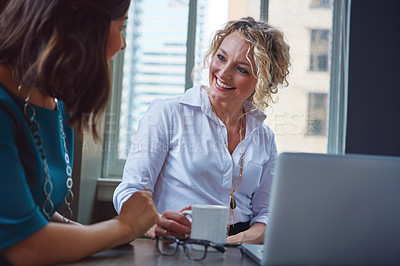 Buy stock photo Shot of two businesswomen using a laptop together in an office