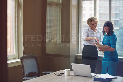 Buy stock photo Shot of two businesswomen going over paperwork together in an office