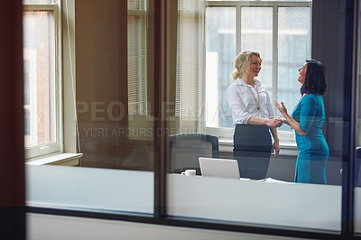 Buy stock photo Shot of two businesswomen shaking hands in an office