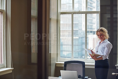 Buy stock photo Shot of a businesswoman reading a report in an office