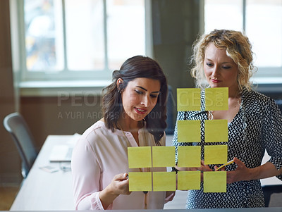 Buy stock photo Shot of two businesswomen brainstorming with adhesive notes on a glass wall in an office