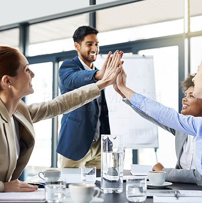 Buy stock photo Shot of a group of businesspeople high-fiving in the boardroom