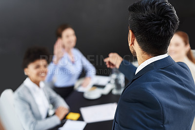 Buy stock photo Shot of a businessman acknowledging his colleague's question during a presentation