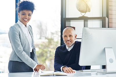 Buy stock photo Shot of two businesspeople using technology in the office