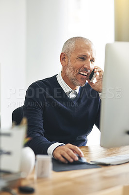 Buy stock photo Cropped shot of a mature businessman talking on his cellphone while using a computer