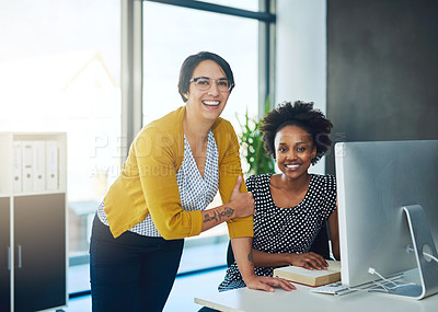 Buy stock photo Portrait of two young businesswomen working together in a modern office
