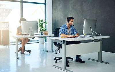 Buy stock photo Shot of two support agents working in a modern office