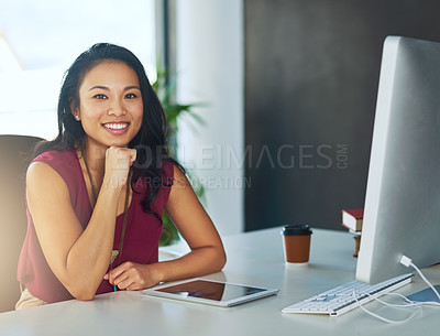 Buy stock photo Portrait of a confident young businesswoman sitting at a desk in a modern office