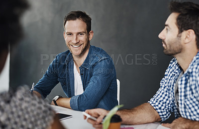 Buy stock photo Portrait of a young businessman sitting in a modern office with colleagues