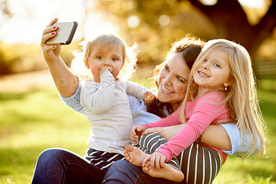 Buy stock photo Shot of a mother taking a selfie with her young daughters at the park