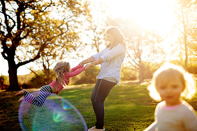Buy stock photo Shot of a mother and her young daughters playing together at the park