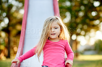 Buy stock photo Cropped shot of a little girl on a slide in the park