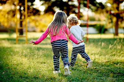Buy stock photo Shot of two young sisters playing together at the park