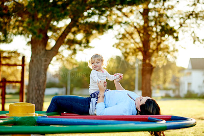 Buy stock photo Cropped shot of a mother and daughter on a merry go round in the park