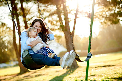 Buy stock photo Full length shot of a mother and daughter on a swing in the park