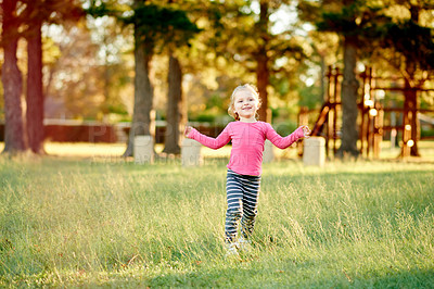 Buy stock photo Shot of an adorable little girl playing in a field of grass at the park
