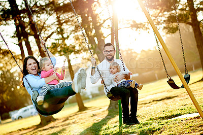 Buy stock photo Full length shot of a young family on the swings in the park