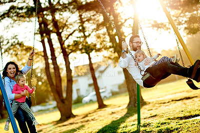 Buy stock photo Cropped shot of a young family on the swings in the park