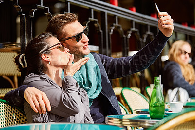 Buy stock photo Shot of a smiling couple talking a selfie while sitting together at a table at a sidewalk cafe