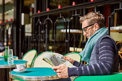 Buy stock photo Shot of a stylish young man reading a map while sitting at a table outside at a sidewalk cafe