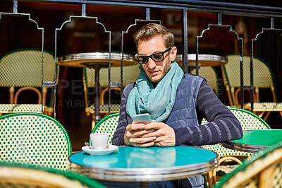 Buy stock photo Shot of a stylish young man using a cellphone while sitting at a table outside at a sidewalk cafe