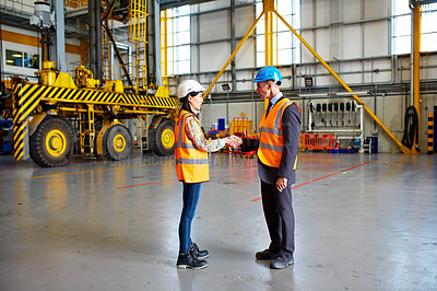 Buy stock photo Shot of two warehouse workers shanking hands together inside of a large warehouse