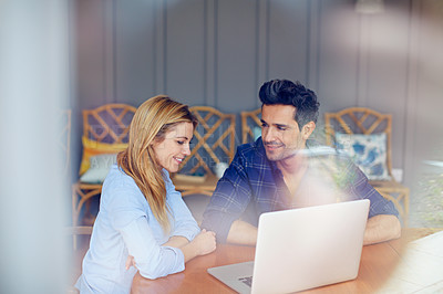 Buy stock photo Shot of a young couple sitting together at their kitchen table using a laptop
