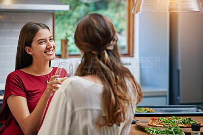 Buy stock photo Shot of two friends hanging out in a kitchen drinking wine together and eating pizza