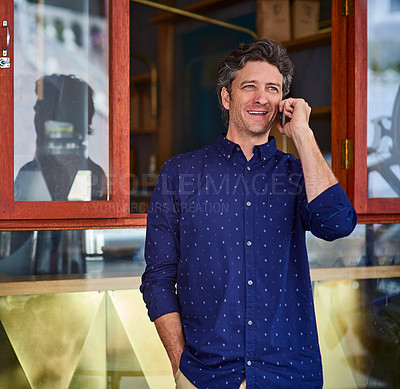 Buy stock photo Shot of a smiling man talking on his cellphone wile standing in front of a cafe