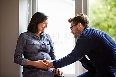 Buy stock photo Shot of a husband rubbing his pregnant wife's tummy at home