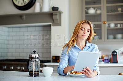 Buy stock photo Shot of a young woman using her digital tablet while sitting in her kitchen at home