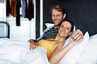 Buy stock photo Portrait of a content couple lying together in bed