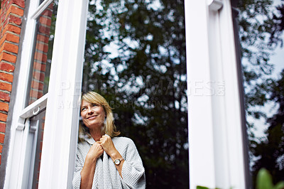 Buy stock photo Shot of a mature woman looking out of her living room window