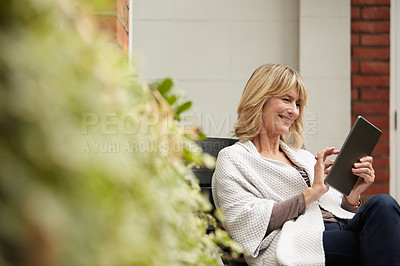 Buy stock photo Shot of a mature woman sitting on her sofa using a digital tablet