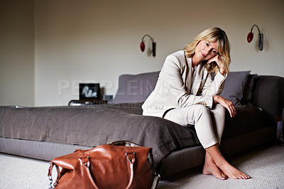 Buy stock photo Shot of a mature businesswoman looking thoughtful while sitting on a hotel bed