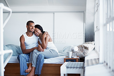 Buy stock photo Shot of a happy young couple sitting on their bed