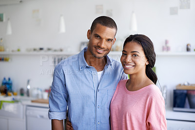 Buy stock photo Portrait of an affectionate young couple standing arm in arm in their home
