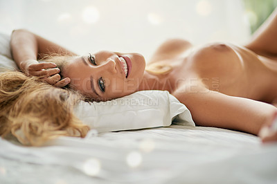 Buy stock photo Shot of a sexy young woman relaxing on a bed in the nude at home