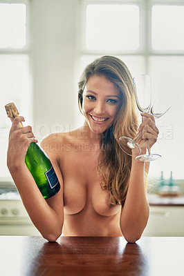 Buy stock photo Portrait of a gorgeous young woman at home holding a bottle of champagne and glasses in the nude