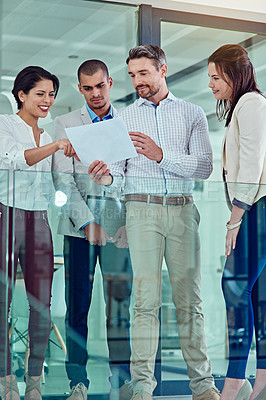 Buy stock photo Shot of a group of coworkers talking over some paperwork in an office