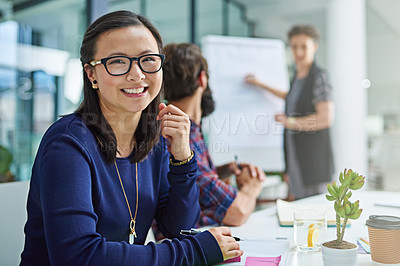 Buy stock photo Portrait of a young businesswoman sitting in a meeting with colleagues in the background