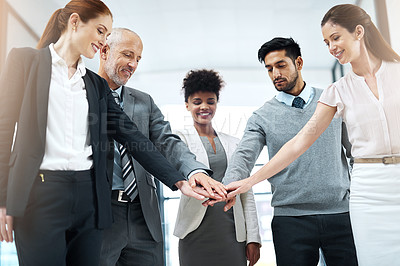 Buy stock photo Shot of a diverse team of colleagues joining their hands together in solidarity