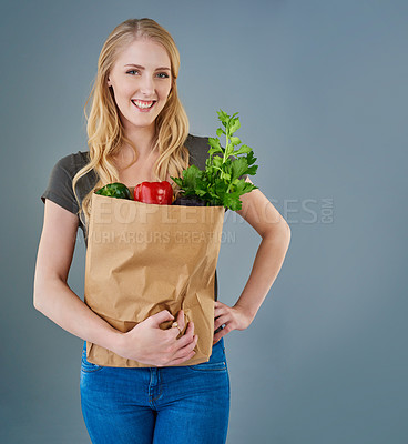 Buy stock photo Cropped studio shot of a young woman holding a paper bag full of vegetables